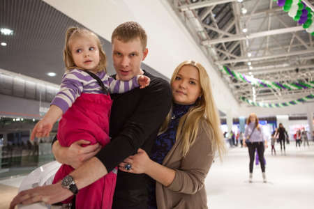 Happy young parents ice skating with their small daughter indoor