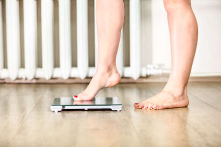 Foto de Caucasian female legs gently tread on the floor scales - Imagen libre de derechos