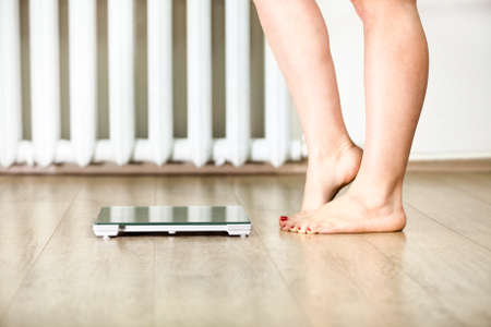 Foto de Caucasian female legs standing in front of weight scales hesitating to stand - Imagen libre de derechos