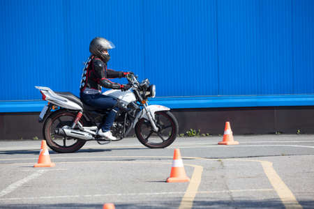 Photo pour Woman L-driver doing exercise around cones on the motorbike in skill training motordrome. Russian driver school - image libre de droit