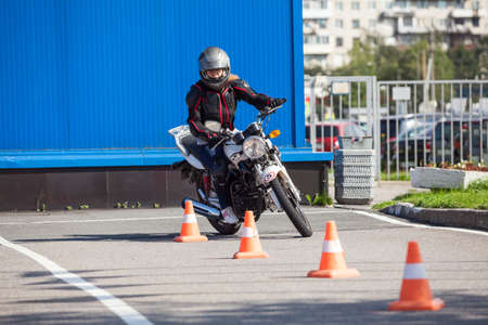 Photo pour L-driver person drives slalom through the orange cones on motordrome on motorcycle - image libre de droit