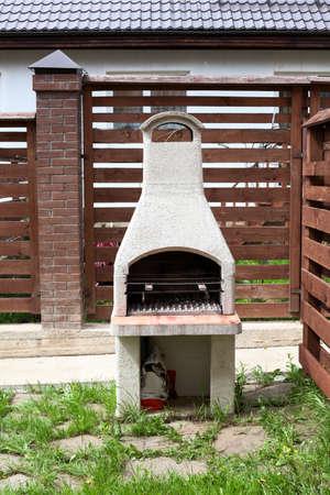 Foto de Stone garden oven for grill or barbeque is in a backyard at summer season - Imagen libre de derechos
