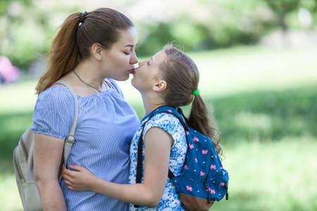 Foto de Mother kissing her daughter while walking in summer park together - Imagen libre de derechos