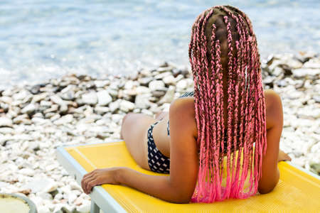 Photo pour Young girl with pink African braids lying back on yellow chaise-longue on sea coast, rear view - image libre de droit
