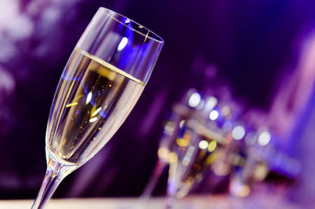 Photo for Luxury party champagne glass in nightclub neon lilac, blue and purple lights, blurry closeup - Royalty Free Image