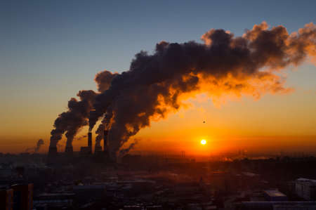 Foto de Power plant pipes with swirling smoke at sunrise, environmental pollution, view against the sun - Imagen libre de derechos