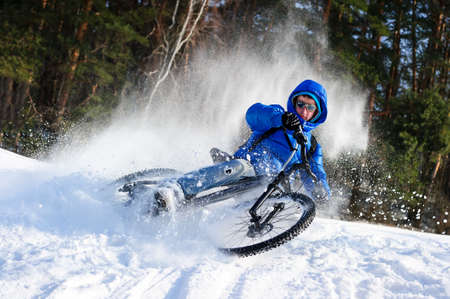 Foto de Cyclist extreme riding mountain bike in flying snow near winter forest in sunny cold day - Imagen libre de derechos