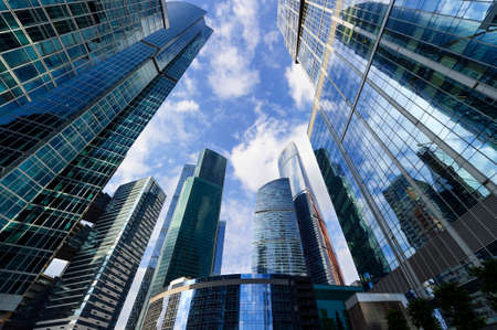 Foto de Modern business office skyscrapers, looking up at high-rise buildings in commercial district, architecture raising to the blue sky with white clouds, bottom view - Imagen libre de derechos