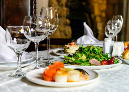 Photo pour Served for holiday banquet restaurant table with dishes, snack, cutlery, wine and water glasses. European food - image libre de droit