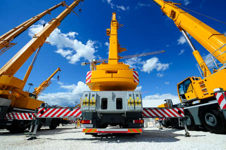 Foto de Mobile construction cranes with yellow telescopic arms and big tower cranes in sunny day with white clouds and deep blue sky on background, heavy industry - Imagen libre de derechos
