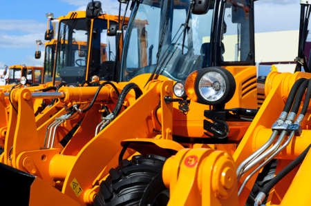 Foto de Bulldozer headlight, row of huge orange powerful construction machines, tractors, excavators, focused on spotlight, heavy industry, blue sky and white clouds on background - Imagen libre de derechos
