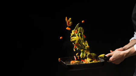 Foto de The chef prepares. Black background for copy text.Concept cooking - Imagen libre de derechos