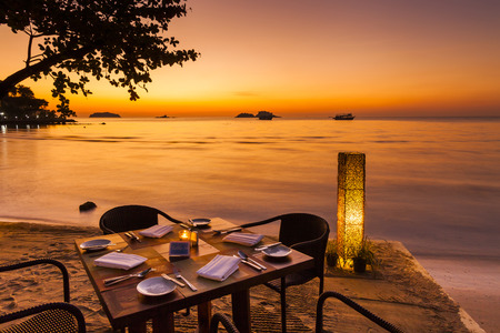 Photo for Romantic sunset on the shore of a tropical island. Cafe on the beach. Koh Chang. Thailand. - Royalty Free Image