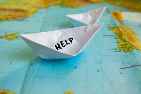 Photo pour White paper boat onto world map with Help sign on it. - image libre de droit