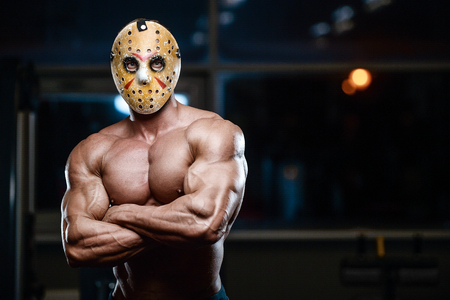 Photo for horror brutal Jason mask man strong bodybuilder athletic fitness man in scary hockey mask in the gym fight warrior in Friday 13th pumping up muscles workout bodybuilding concept background - Royalty Free Image