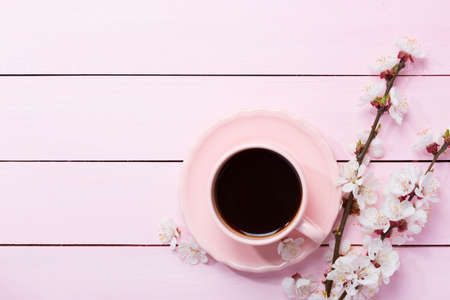 Photo for Cup of coffee and spring  flowers  on pink wooden table. - Royalty Free Image