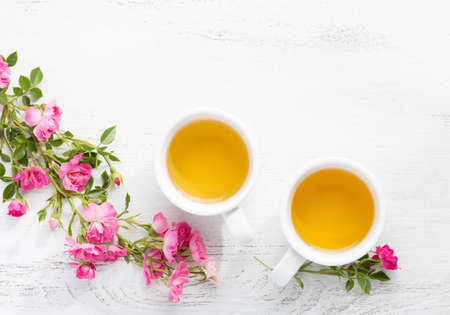 Photo for Two cups  of tea and branch of small pink roses on rustic table. - Royalty Free Image