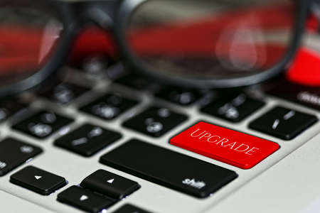 Foto de Updating software applications or computer hardware concept - laptop keyboard with red UPGRADE button instead of enter key and nifty sunglasses on it. Close-up capture, selective focus. - Imagen libre de derechos