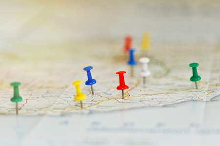 Foto de Map of a sea shore with route highlights and places of interest marked by colored pins. Vacations preparations idea, route planning concept. Close-up capture, selective focus, unrecognizable names. - Imagen libre de derechos