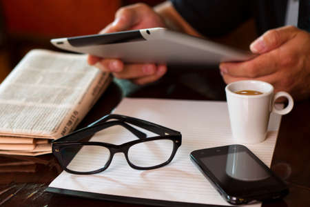 Photo for Newspapers and coffee cup, reading glasses, striped paper, hands holding tablet, cell phone. - Royalty Free Image