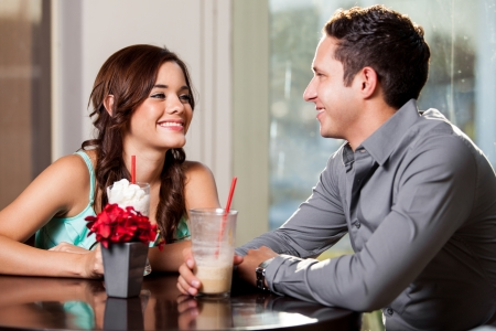 Photo for Cute Latin woman falling in love with a guy on a date at a restaurant - Royalty Free Image