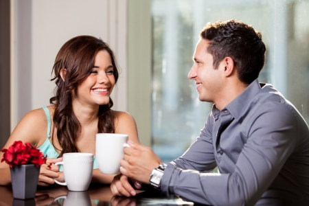 Photo for Happy brunette and her attractive date having fun and drinking coffee at a restaurant - Royalty Free Image