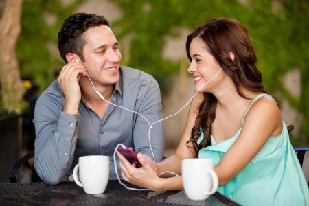 Foto de Happy Hispanic couple listening to some music while having coffee on a date - Imagen libre de derechos