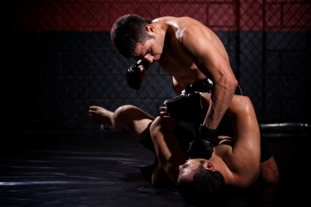 Strong MMA fighter holding his rival down and throwing punches at him during a fight  With plenty of copy space