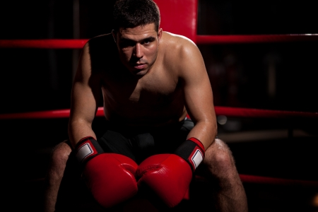 Dramatic portrait of a young Hispanic boxer sitting on his corner of the ring with some copy space