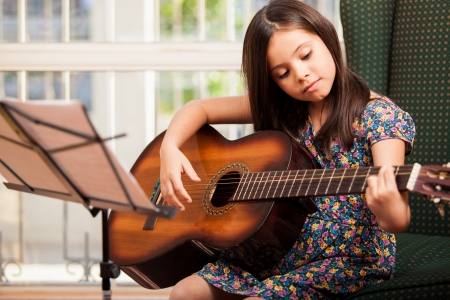 Photo for Pretty little girl practicing some new sound on a guitar at home - Royalty Free Image