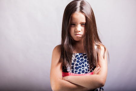 Photo pour Portrait of a little brunette with arms crossed and acting all mad on a white background - image libre de droit