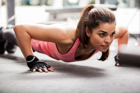Photo for Beautiful Latin woman doing push ups in the gym before lifting some weights - Royalty Free Image