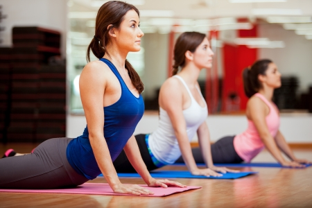 Photo pour Cute Hispanic women practicing the cobra pose during their yoga class in a gym - image libre de droit