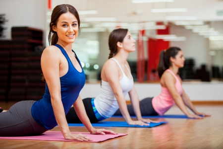 Beautiful young woman trying the cobra pose and smiling during yoga class
