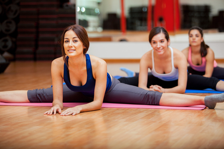 Photo pour Group of women working on their flexibility and doing some leg splits in a gym - image libre de droit