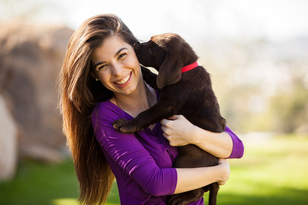 Photo pour Happy young woman hugging and having fun with her Labrador puppy outdoors - image libre de droit