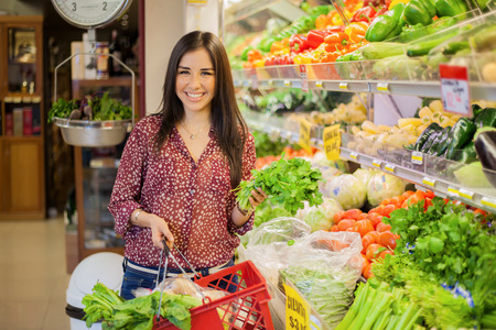 Photo pour Happy young brunette carrying a shopping basket and picking some vegetables at the grocery store - image libre de droit