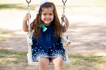 Beautiful little brunette on a swinging chair at a park  Plenty of copy space