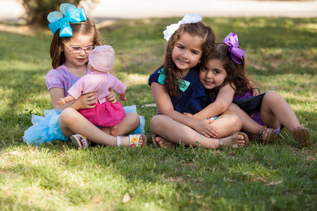 Beautiful little girl playing with her doll while ignoring her friends at a park