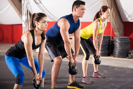 Photo for Three people working out with kettlebells in a crossfit gym - Royalty Free Image
