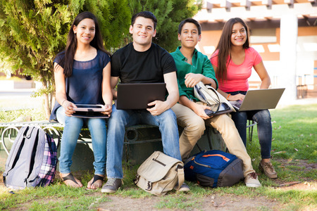 Foto de Group of high school students using all kinds of devices while hanging out - Imagen libre de derechos