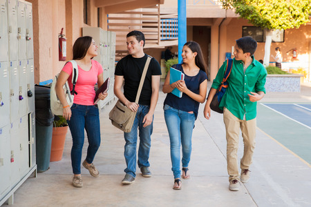 Photo for Group of high school students talking and laughing in a hallway between classes - Royalty Free Image