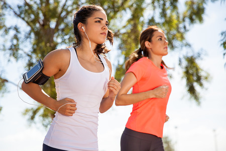 Photo pour Two female runners working out while listening to music on their mobile phone on an armband - image libre de droit