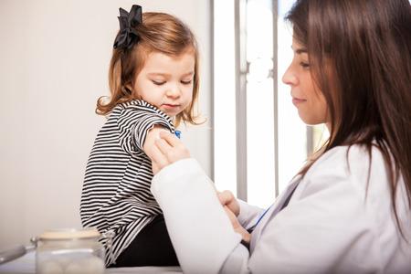Foto de Profile view of a female pediatritian rubbing alcohol on a little girl - Imagen libre de derechos