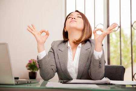 Photo pour Stressed young business woman doing some breathing exercises and meditating at her office - image libre de droit
