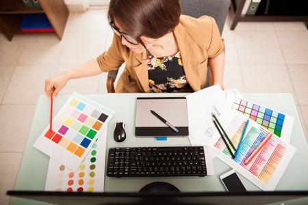 Foto de Top view of a young graphic designer working on a desktop computer and using some color swatches - Imagen libre de derechos