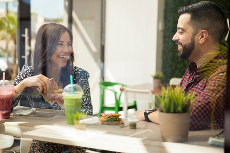 Photo for Attractive young Hispanic friends having sandwiches and smoothies for lunch - Royalty Free Image