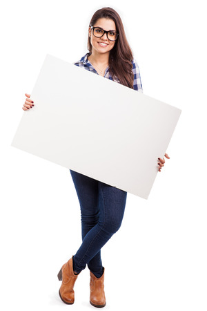 Photo for Gorgeous young Hispanic woman wearing glasses and holding a big white sign - Royalty Free Image