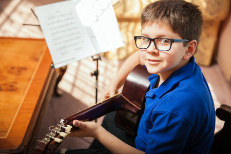 Photo for Portrait of a young boy with glasses practicing a song during a guitar lesson at home - Royalty Free Image