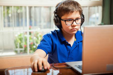 Foto de Portrait of a young boy with glasses playing some video games on a laptop computer - Imagen libre de derechos